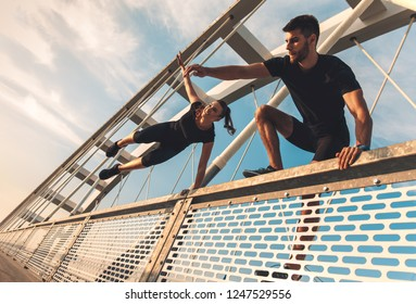 Young couple in black sports outfit doing morning workout outdoors. Young man and woman jumping over the fence together.