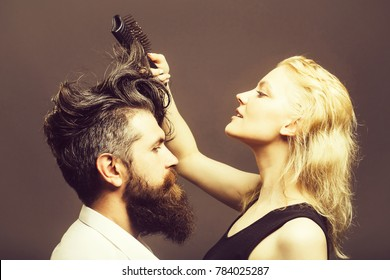 young couple of blonde pretty hairdresser combing with brush male brunette hair of handsome bearded man with long beard in white shirt on grey background
