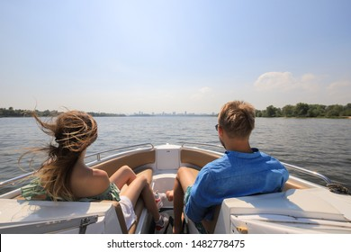 Young couple boating on a motor boat. Boy with girl on the boat enjoy cruise trip.