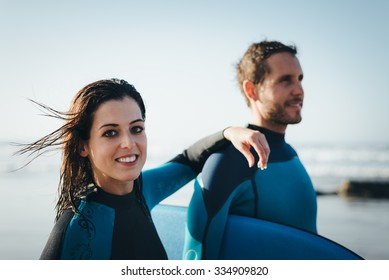 Young couple of bodyboard surfers. Surfing and outdoor sport lifestyle concept. Woman and man after bodyboarding.