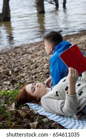 Young couple with book on the river bank in spring