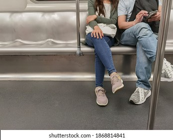 young couple (boy and girl friends) sit in spacious public subway train in Hong Kong, China, man playing mobile phone