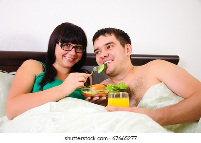 Young couple at breakfast in bed together early in the morning.