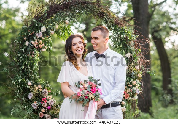 Young couple, bride and groom in the forest at sunset. Wedding decor, a large wreath of twigs and flowers.