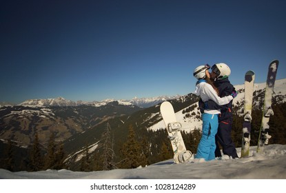 Young couple in bright clothes and helmets with snowboard and ski aside kissing on background of snowy mountains, bright blue sky, Alps Austria