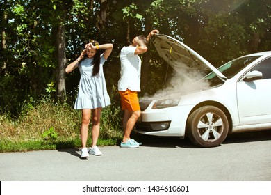 The young couple broke down the car while traveling on the way to rest. They are trying to fix the broken by their own or should hitchhike, getting nervous. Relationship, troubles on the road