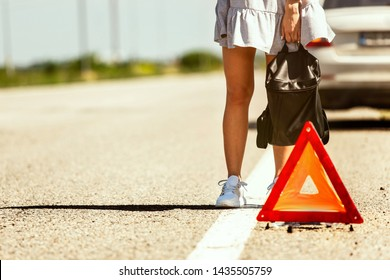 The young couple broke down the car while traveling on the way to rest. They are trying to stop other drivers and ask for help or hitchhike. Relationship, troubles on the road, vacation.
