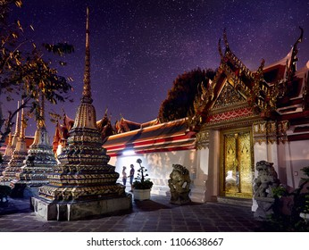 Young Couple in Buddhist temple complex Wat Pho in Bangkok at magical night starry sky at background in Thailand