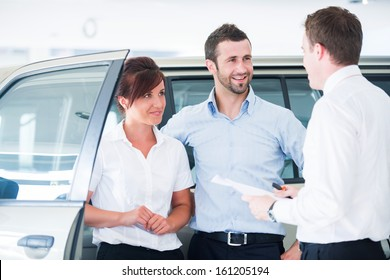 Young couple buying automobile from salesman in a car salon