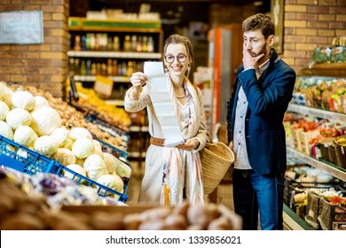 Young couple buying food standing together with long shopping list in the vegetable department of the supermarket. Man with shocked emotions