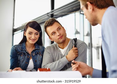 Young couple buying new home, talking with salesman