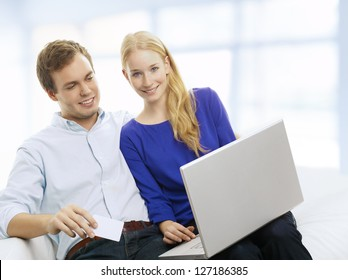 Young couple buying on internet by credit card. THey using computer for shopping at home .