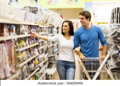 young couple buying padlock in hardware store