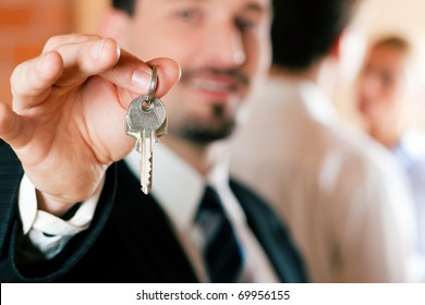 Young couple buying or renting a home or apartment, they are meeting the owner or real estate broker who has the keys; FOCUS on keys