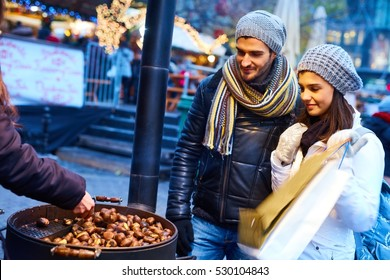 Young couple buying roasted chestnuts at wintertime on the street.