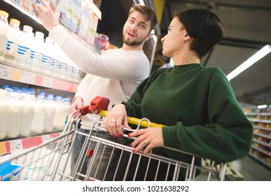 A young couple buys dairy products at a supermarket. Portrait of young people with shopping carts. Family shopping at a supermarket.