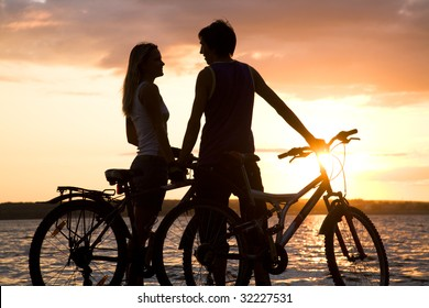 Young couple by lake with their bicycles and looking at each other in the evening