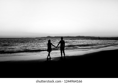 Young couple by the sea during sunset. Black and white photograp