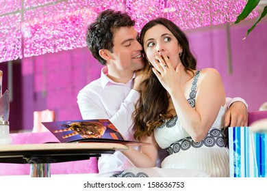 Young Couple in a Cafe or Ice cream parlor, looking together in the menu ordering food