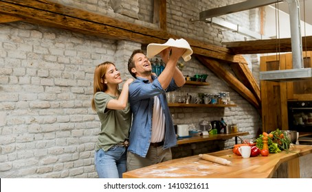 Young couple caking pizza in rustic kitchen together