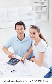 Young couple with a calculator at home