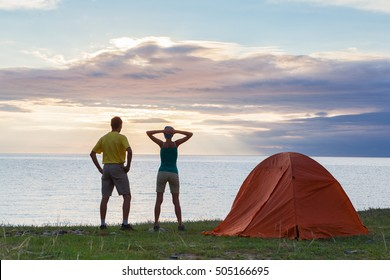 Young couple at the camping enjoying of sea view in a sunny day