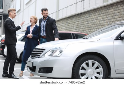 Young couple with car dealer outdoors