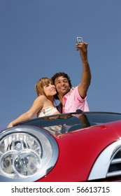Young couple in a car taking a photography with a mobile phone