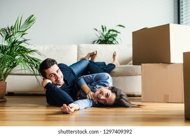 A young couple with cardboard boxes moving in a new home.