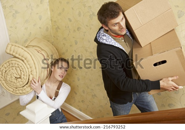 Young couple carrying cardboard boxes and a mattress