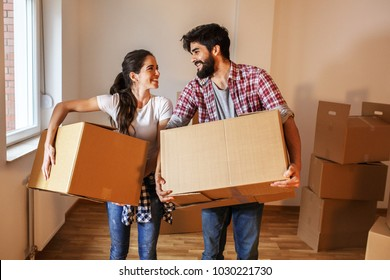 Young couple carrying cardboard  full of home essentials into a new home.Moving house.Real estate concept.