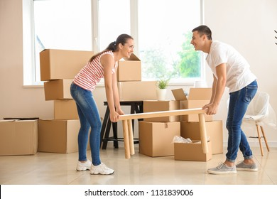 Young couple carrying table in room after moving to new home