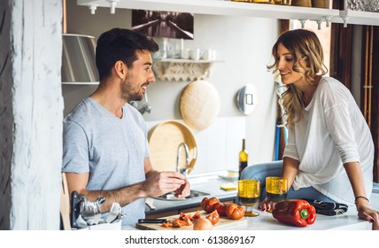 Young couple in casual clothing cooking together at kitchen and talking.