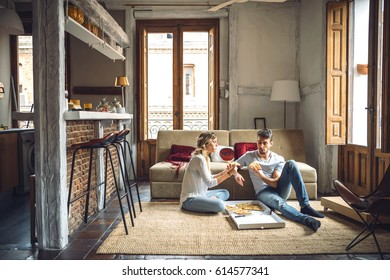 Young couple in casual clothing eating ordered pizza while sitting on floor in living room.