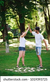 A young couple celebrate victory playing tic-tac-toe in the park