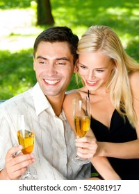 Young couple celebrating with champagne together, outdoors. Love, flirt, romantic, relations, celebration theme concept.