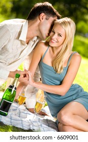 Young couple celebrating with champagne together, at picnic