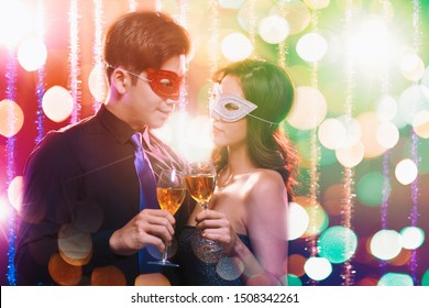 young Couple celebrating New Year and drinking champagne on masquerade party