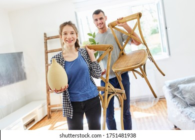 Young couple with chairs and plants moving in and setting up the new apartment