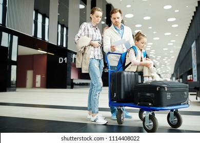 Young couple checking tickets before departure while pushing luggage cart with their daughter and suitcase