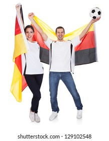Young couple cheering for Germany. Isolated on white
