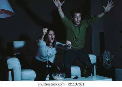 Young couple cheering their sports team watching game on TV