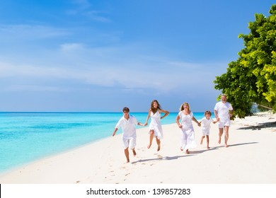Young couple with a child and grandparents running on a beach