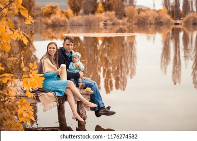 A young couple with a child resting on a wooden dais near a lake. Tea in the nature. Warm autumn weather