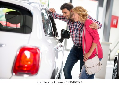 Young  couple chooses to buy a car in car dealership saloon