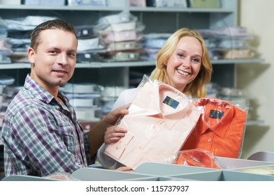 Young couple choosing business shirt during clothing shopping at sales store