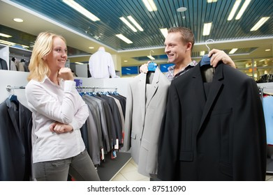 Young couple choosing business suit during clothing shopping at sales store