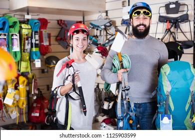 Young couple choosing climbing equipment in sports equipment store