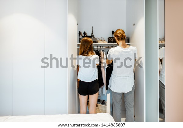 Young couple choosing clothes, standing back at the wardrobe in the bedroom