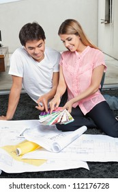 Young couple choosing colors from swatches while sitting on rug with blueprints